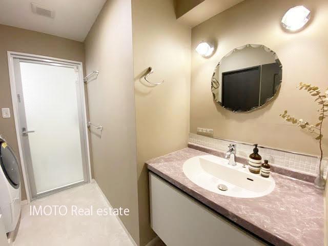丸い鏡が特徴的。優しい色合いの洗面室
